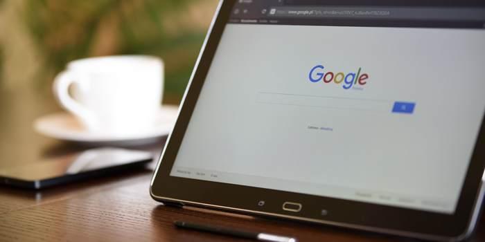 Tablet con schermata di google e tazza vicino