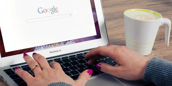 Donna che scrive al pc nella barra di ricerca di Google