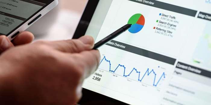 Uomo che controlla il cellulare e con la penna indica sul tablet un grafico a torta