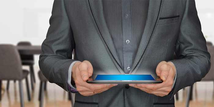 uomo in giacca e cravatta che mantiene un tablet con lo schermo rivolto verso l'alto
