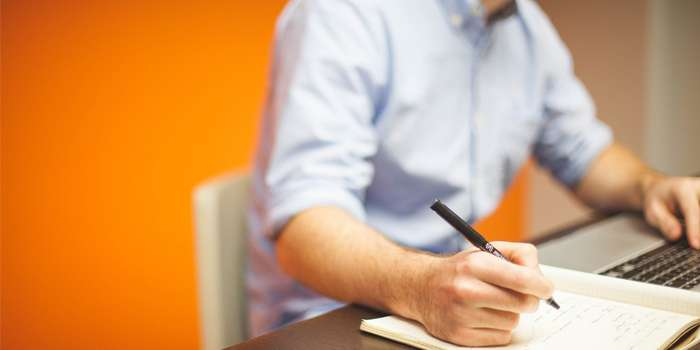Uomo che legge informazioni sul pc e prende appunti sul quaderno