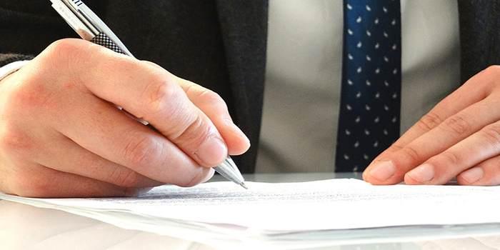 Avvocato che scrive il contratto con la penna su più fogli di carta