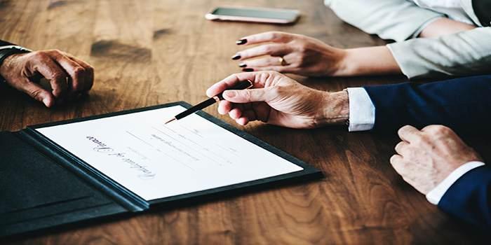 Avvocato che indica dove firmare ad una donna e un uomo