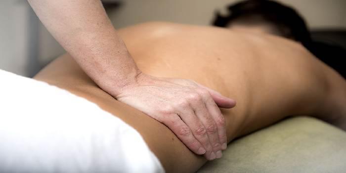 Mani del fisoterapista che esegue il massaggio alla schiena al cliente disteso sul lettino