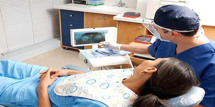 dentista che fa vedere alla paziente stesa sul lettino la panoramica della sua radiografia