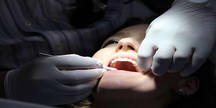 Dentista che apre la bocca ad una donna tenendo da una parte la bocca aperta e dall'altra impugna l'attrezzo