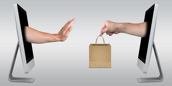 tablet con mani che escono dallo schermo e si passano una shopper