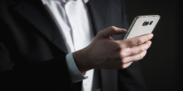 uomo che tiene in mano un cellulare