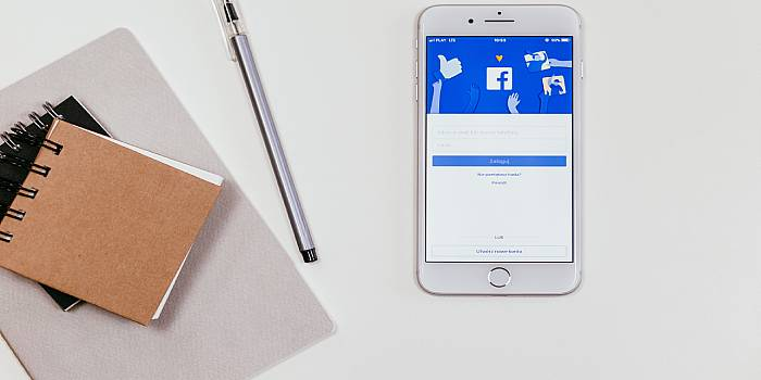 cellulare che si connette a Facebook con penna e quaderno a lato