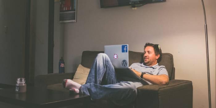 persona seduta sul divano con pc