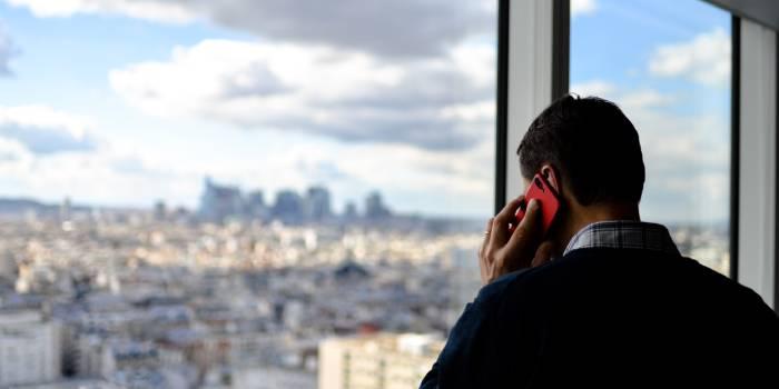 uomo al cellulare che guarda fuori la finestra