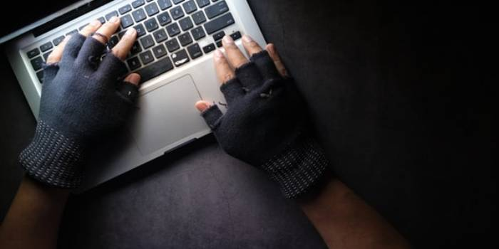 persona con guanti neri che scrive al pc